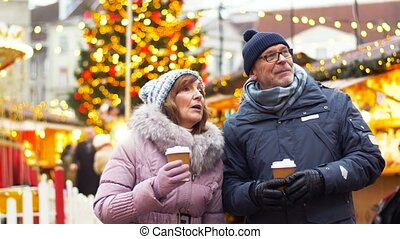 senior couple with hot drinks at christmas market - winter...
