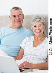 Senior couple with laptop in bed