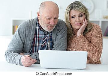Senior couple with laptop