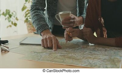 Senior couple with map at home, making plans. -...