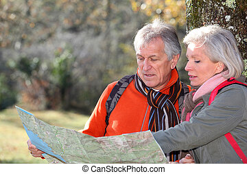 Senior couple with map on a hiking day