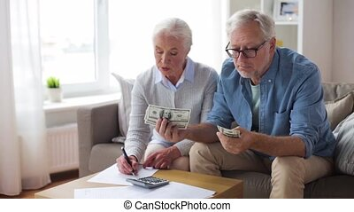 senior couple with money and bills at home - family,...