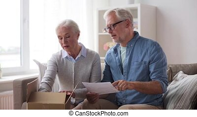 senior couple with parcel and delivery note