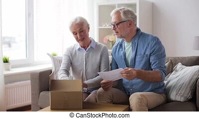 senior couple with parcel and delivery note - delivery, mail...