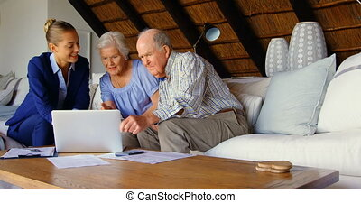 Senior couple with real estate agent discussing over laptop ...