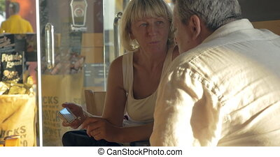 Senior couple with smart phone in cafe
