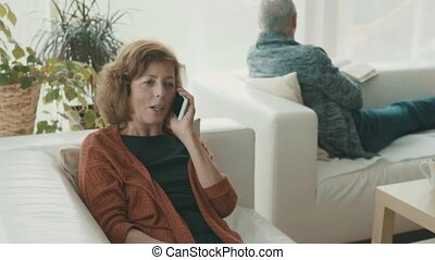 Senior couple with smartphone relaxing at home. - Happy...
