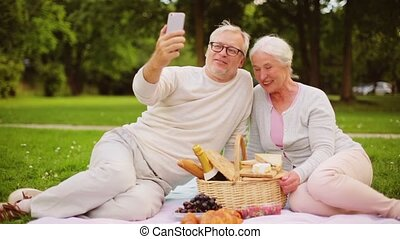 senior couple with smartphone video chat at picnic - old...