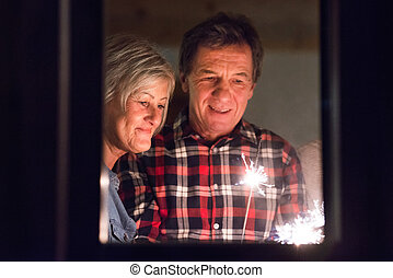 Senior couple with sparklers at Christmas time having fun.