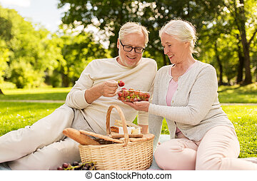 senior couple with strawberries at picnic in park - old age,...