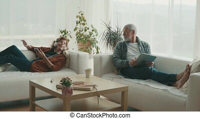 Senior couple with tablet and smartphone relaxing at home. -...