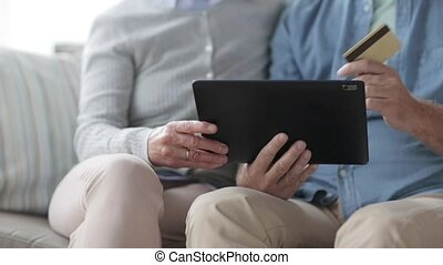 senior couple with tablet pc and credit card - family,...