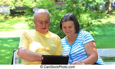Senior couple sitting on a bench in the park and working on digital tablet pc