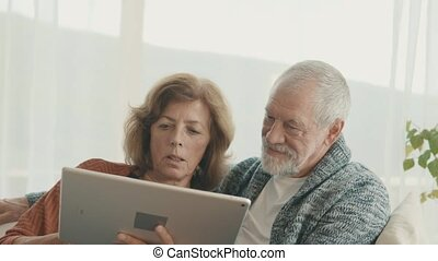 Senior couple with tablet relaxing at home. - Happy senior...