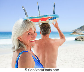Senior couple with their surfboard