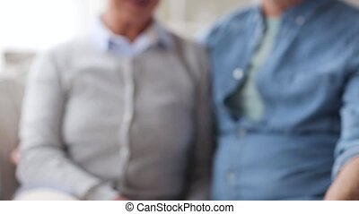 senior couple with tv remote at home