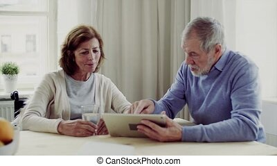 Senior couple with wheelchair and tablet sitting at the table at home, talking.