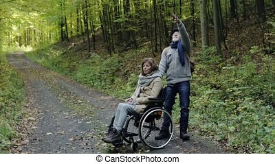 Senior couple with wheelchair in autumn forest. - Active...