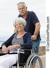 senior couple with wheelchair on a walk