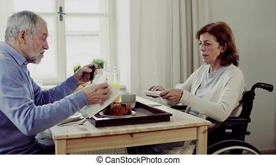 Senior couple with wheelchair sitting at the table at home, having breakfast and talking.