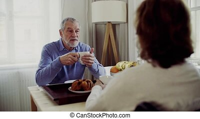 Senior couple with wheelchair sitting at the table at home,...