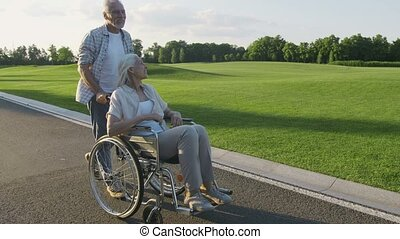 Senior couple with wife in wheelchair on a walk