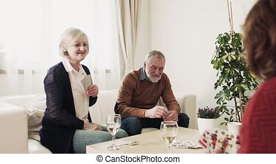 Senior couples playing cards with friends at home.