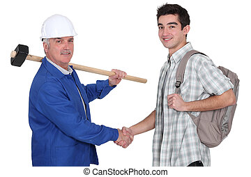 senior craftsman and apprentice shaking hands