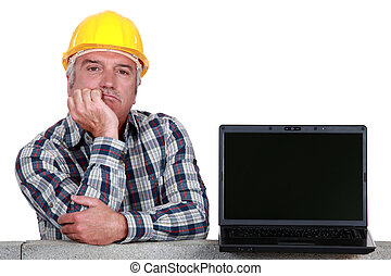 senior craftsman posing next to a laptop