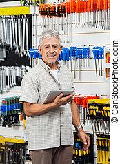 Senior Customer Holding Tablet Computer In Hardware Shop