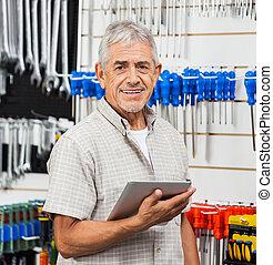 Senior Customer Holding Tablet Computer In Hardware Store