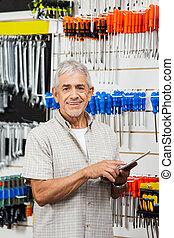 Senior Customer Using Tablet Computer In Hardware Shop