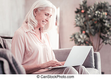 Senior cute woman spending time with using the laptop.