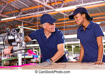 senior cutter teaching young worker cutting fabric -...
