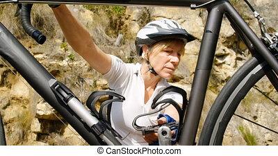 Senior cyclist checking bicycle at countryside 4k - Active ...