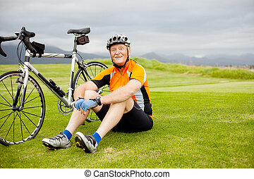 senior cyclist - happy senior cyclist sitting on grass...