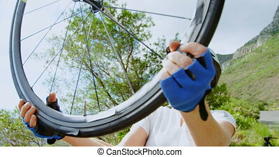 Senior cyclist repairing bicycle at countryside 4k - Active ...