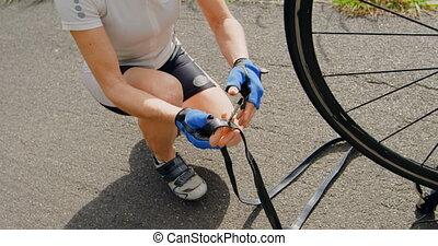 Senior cyclist repairing bicycle on road 4k - Senior cyclist...