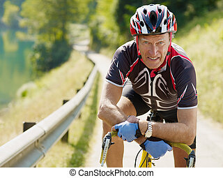 senior cyclist - senior man leaning on road bike, looking at...