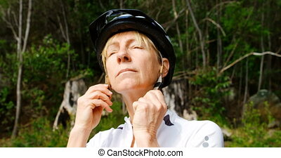 Senior cyclist wearing bicycle helmet at countryside 4k - ...