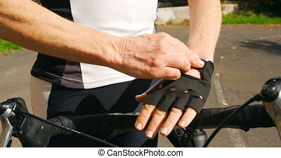 Senior cyclist wearing fingerless gloves at countryside 4k...