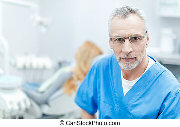 senior dentist looking at camera in dental clinic with patient behind