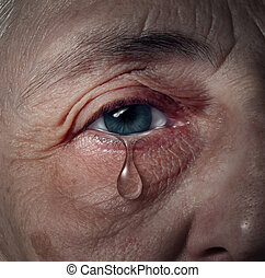 Senior depression and elderly mental health issues related to loneliness and emotional illness based on grief or chemical imbalance causing anxiety as a close up of an aging human eye crying a tear drop.