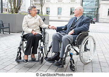 senior disabled couple holding hands
