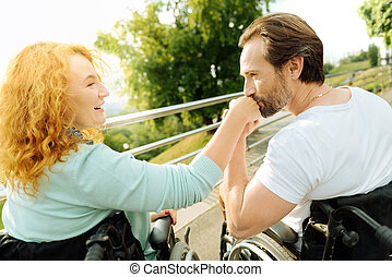 Senior disabled man kissing a hand of his loving wife