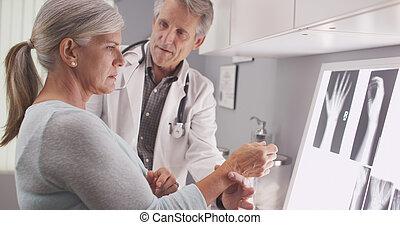 Senior doctor assessing injury - Senior male doctor...
