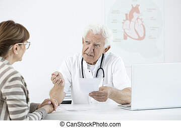 Senior doctor consulting with patient