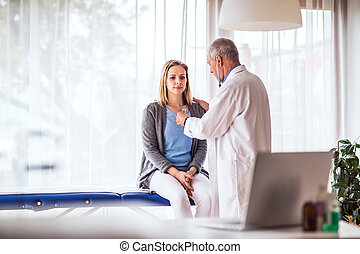 Senior doctor examining a young woman in office.