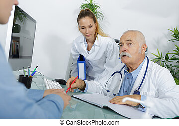 Senior doctor in conversation with patient
