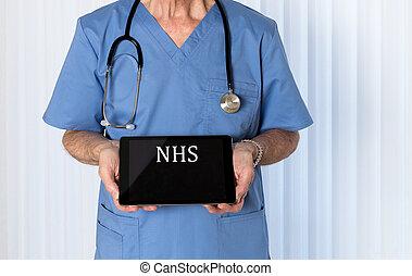 Senior doctor in scrubs facing camera